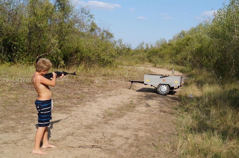 мальчик участвует в игре на природе стреляет из винтовки по бутылке