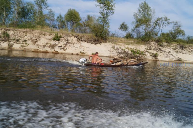 Костёр на берегу реки. Дрова для костра. Сбор валежника, собранный валежник перевозится на лодке